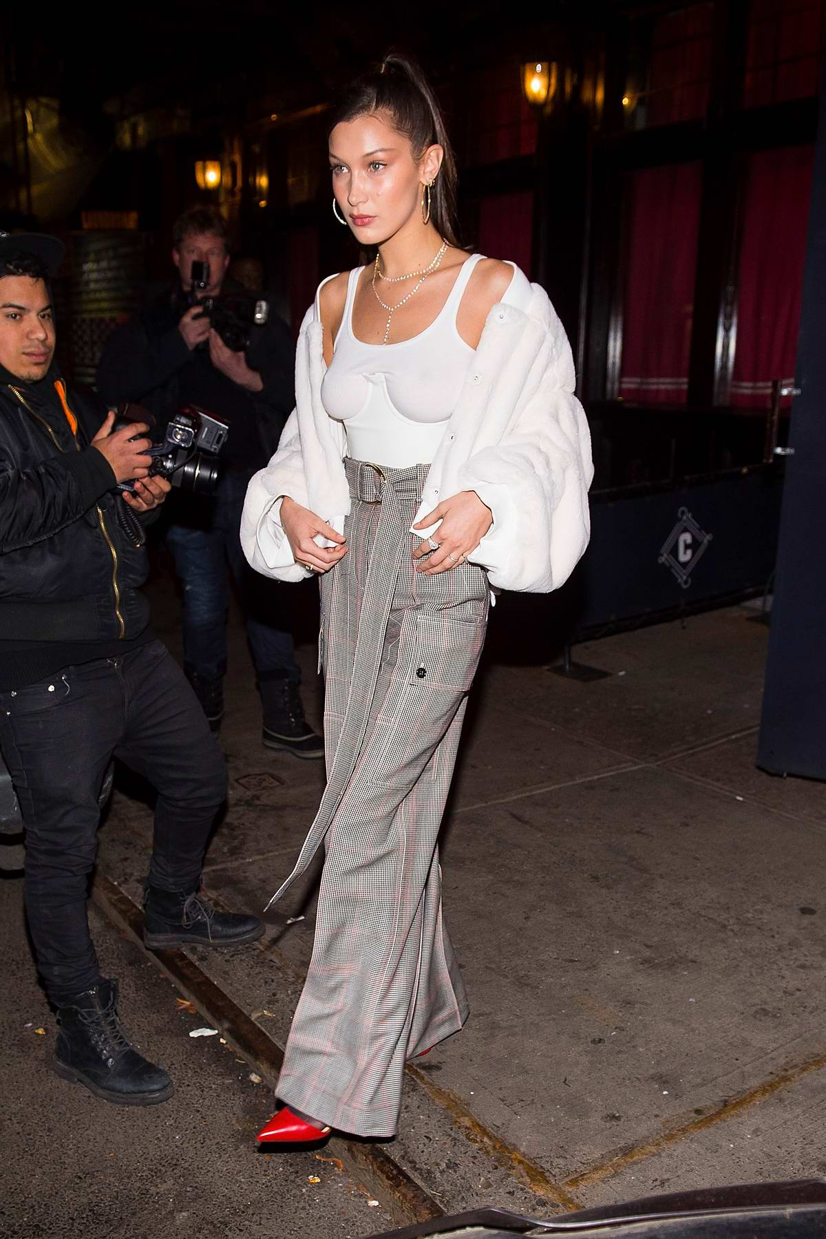 Bella Hadid wears a white jacket over a vest top while heading for a night out in New York City