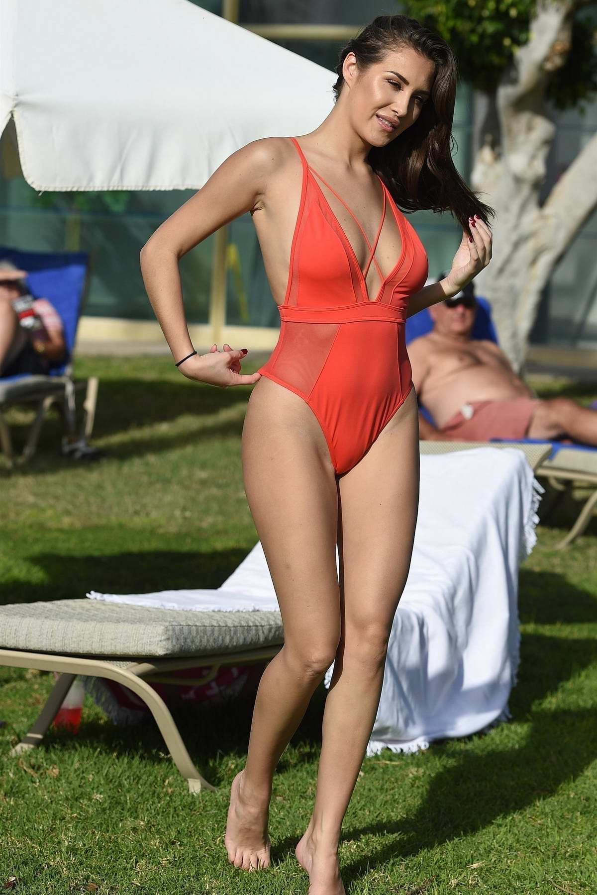 Chloe Goodman wears an orange swimsuit as she catches some sun during her holiday in Malta