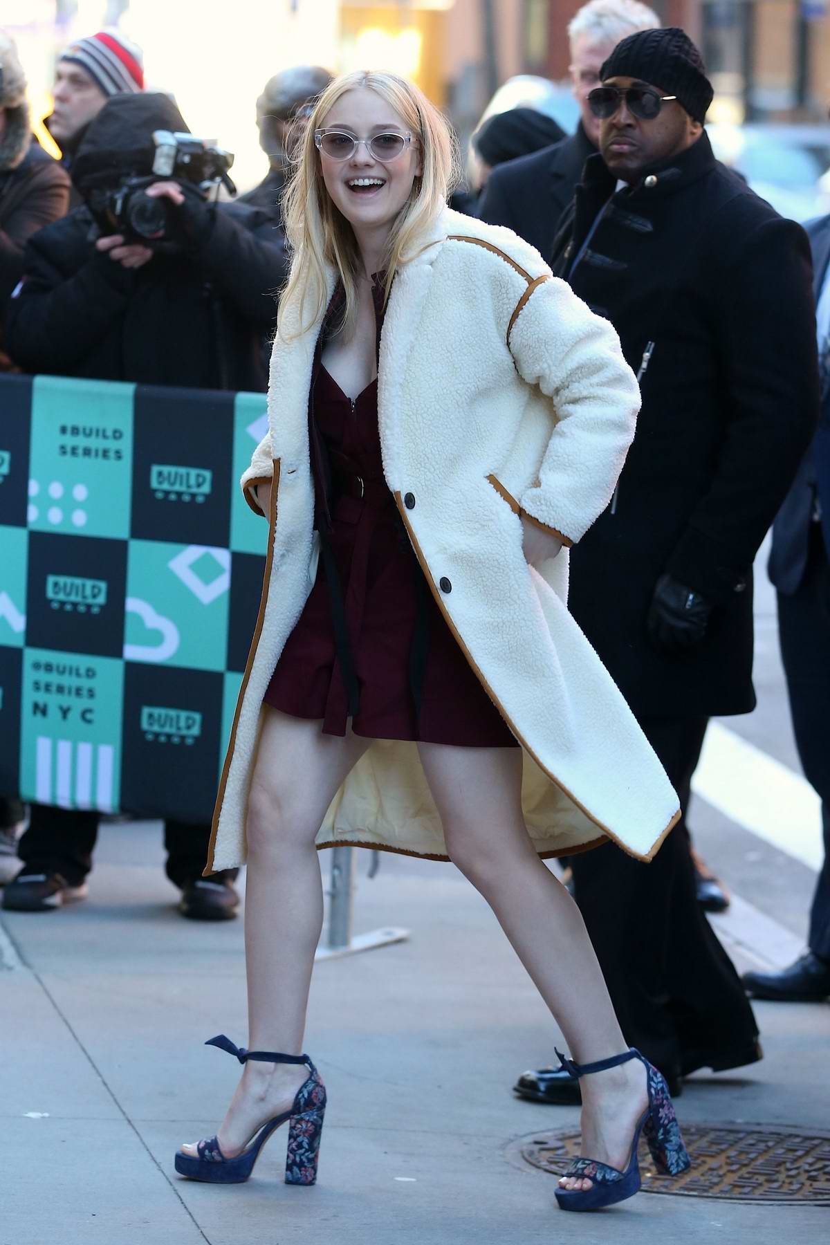 Dakota Fanning visits the AOL Build Speaker Series wearing a short cocktail dress and long coat in New York City