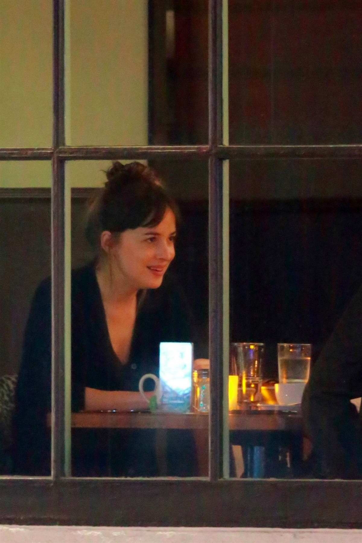 Dakota Johnson enjoys a candle lit dinner with a friend at Hugo's Cafe in Canyon Country, California