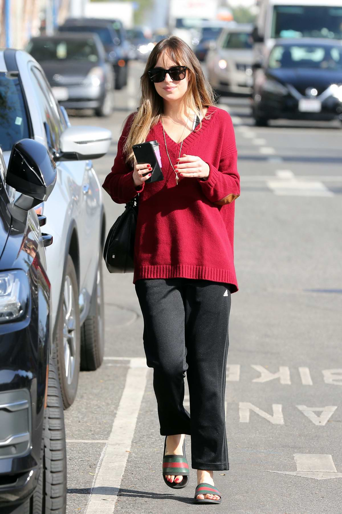 Dakota Johnson wears a red jumper and black adidas pants while out grabbing a coffee with a her friend in West Hollywood, Los Angeles