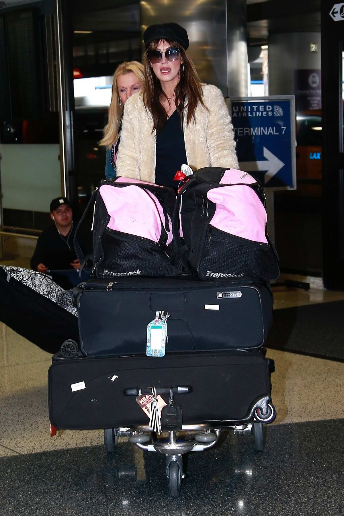 Delta Goodrem carts heavy luggage as she makes her way through LAX airport in Los Angeles