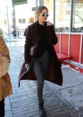 Gigi Hadid keeps herself warm in a maroon coat over a sweater paired with patterned pants on an extremely cold day in New York City