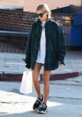 Hailey Baldwin wearing an over-sized green plaid shirt over a white t-shirt while she grabs some lunch in Los Angeles