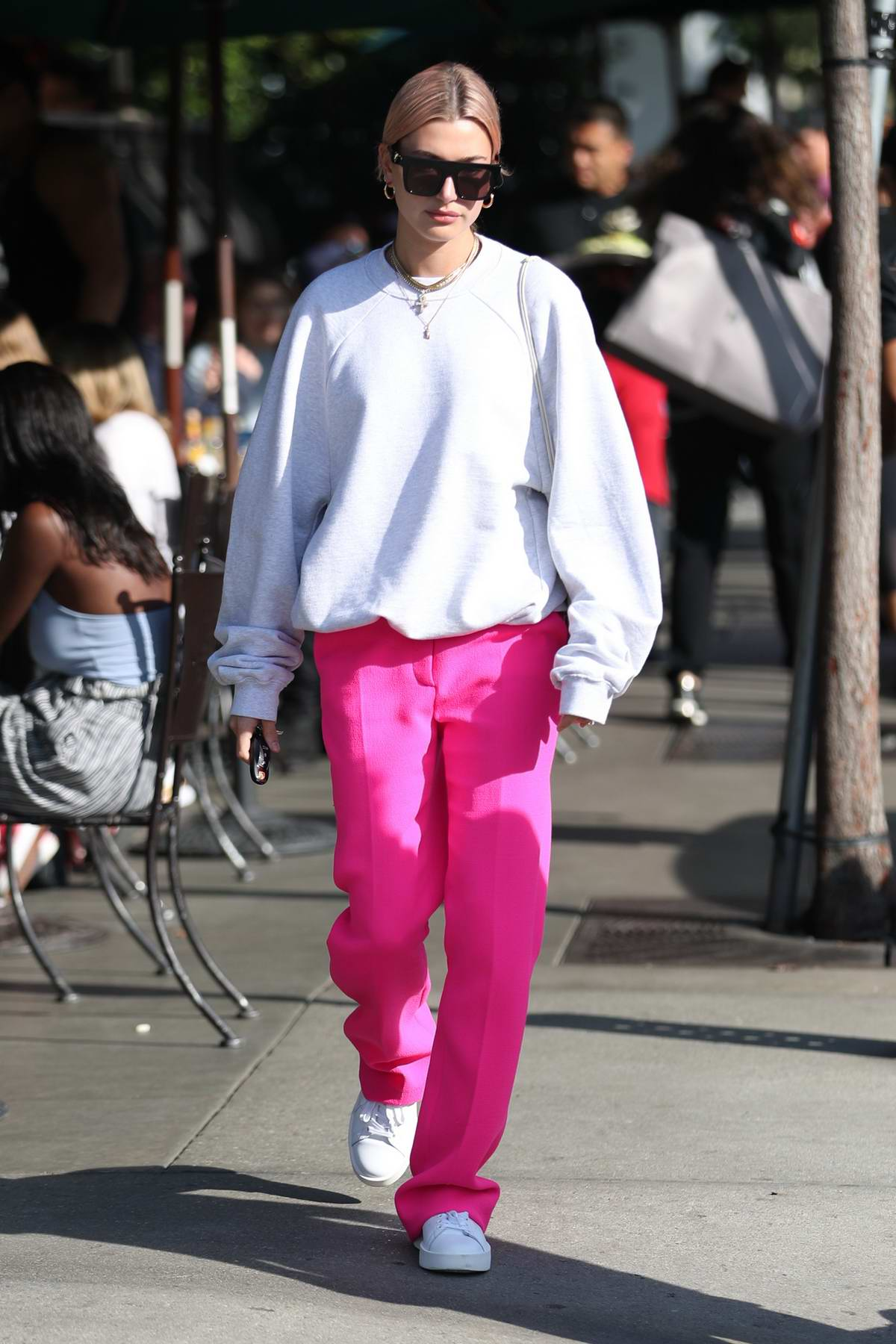 Hailey Baldwin wears bright pink pants and white sweatshirt to lunch at Urth Caffe in West Hollywood, Los Angeles