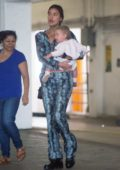 Irina Shayk steps out in a snakeskin print outfit while cradling her daughter in Los Angeles