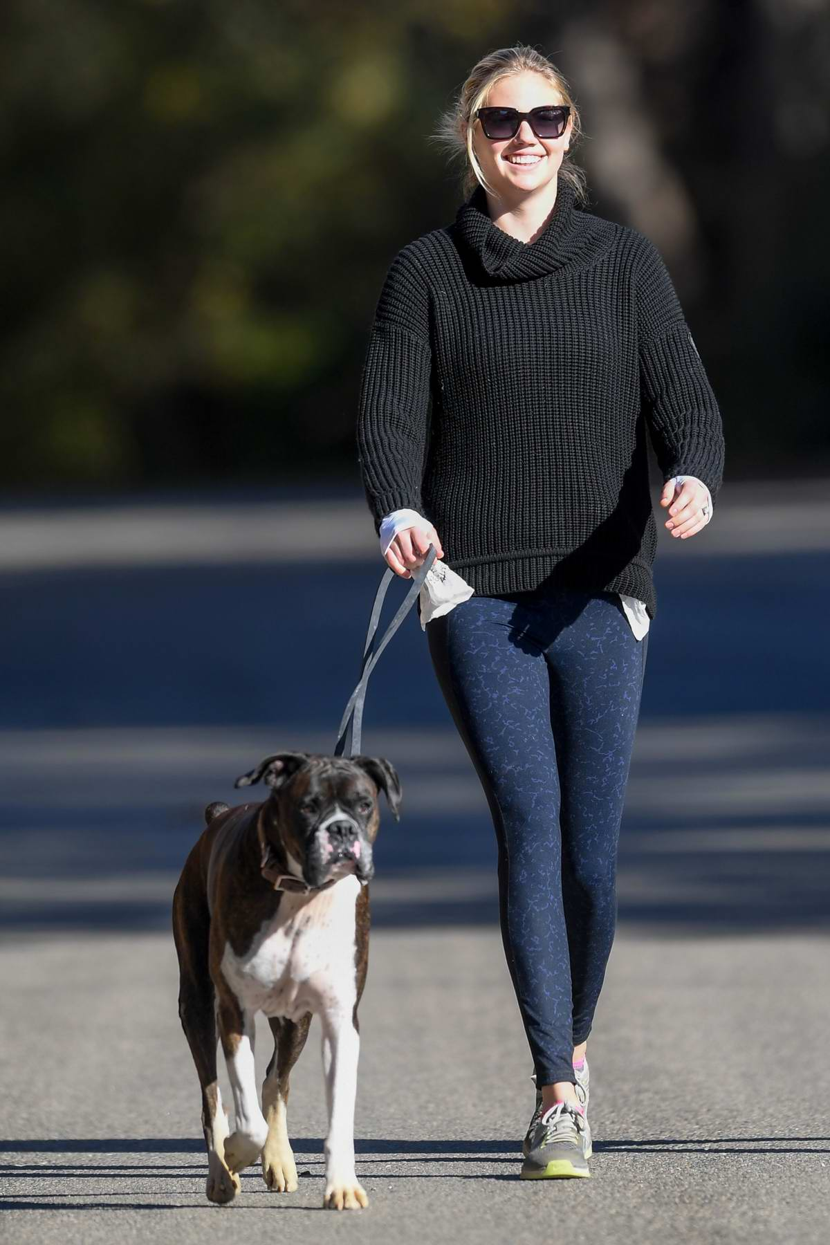 Kate Upton out for a stroll with her dog wearing a black turtleneck sweater and blue leggings in Los Angeles