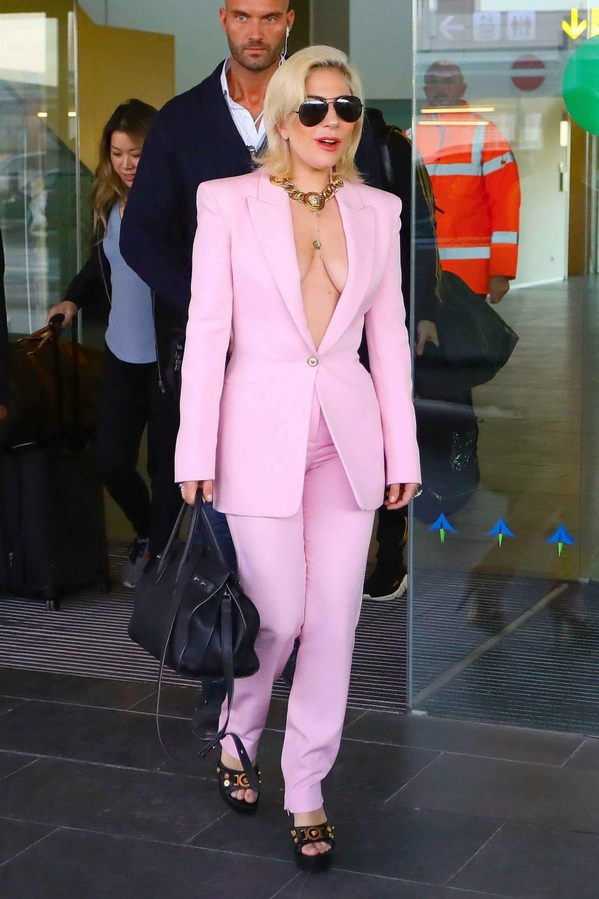 Lady Gaga dressed in a pink pantsuit arrives at Barcelona-El Prat Airport in Barcelona, Spain