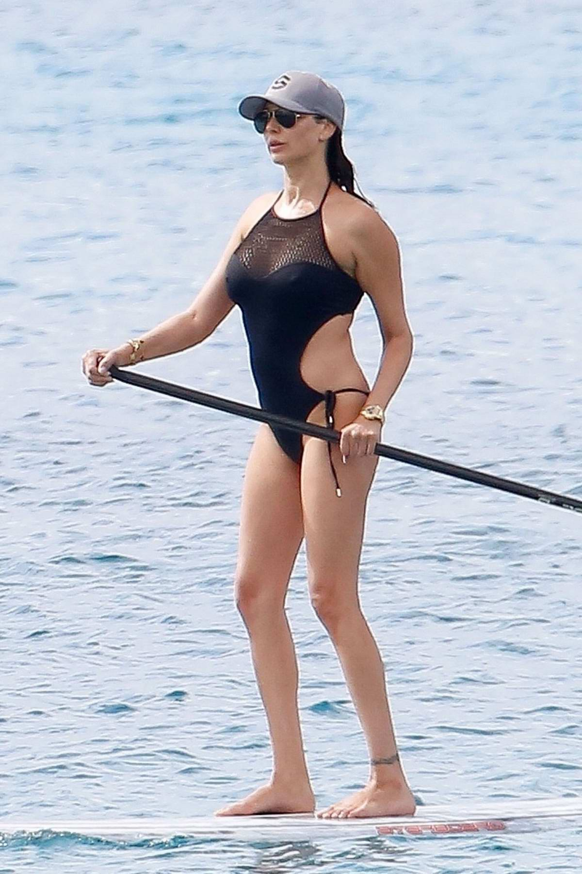 Lauren Silverman enjoys some paddle boarding wearing a black swimsuit in Barbados