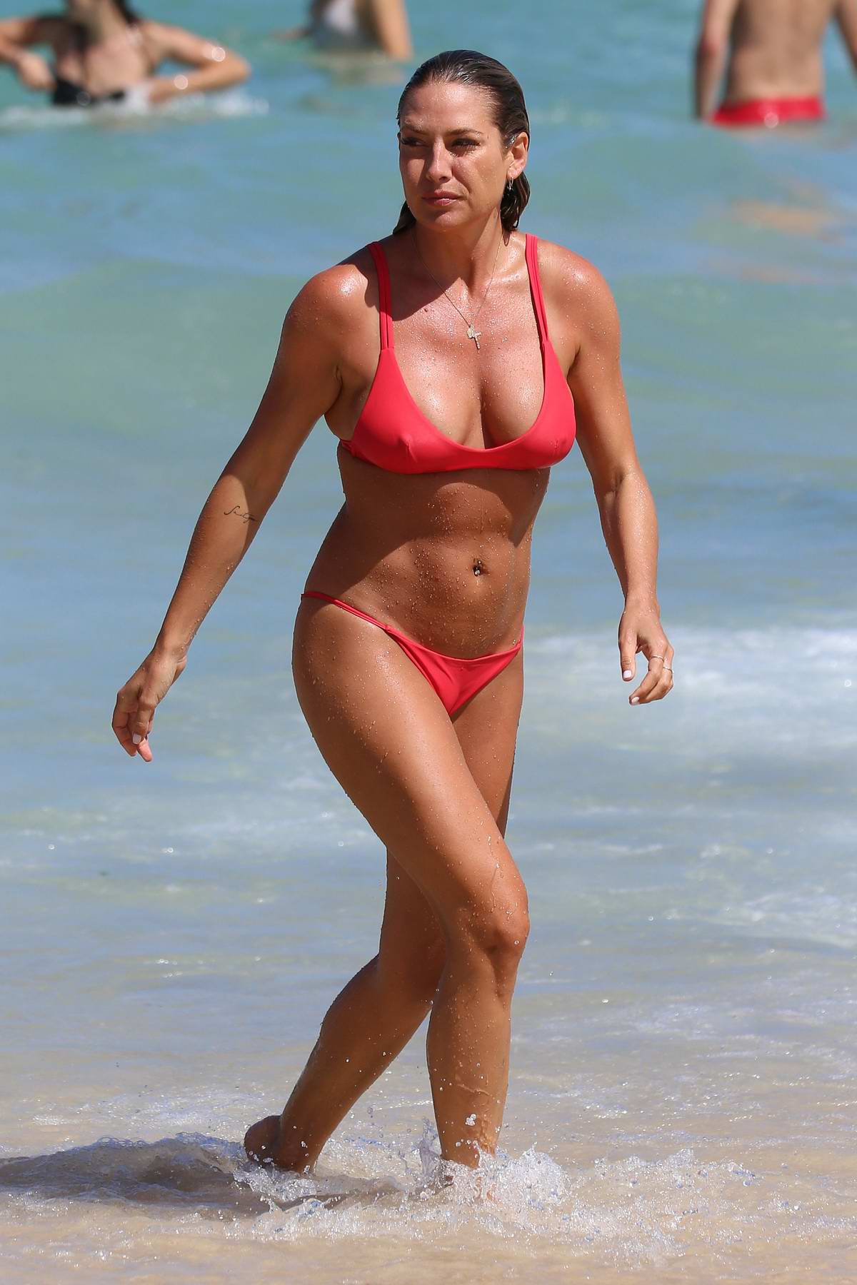 Lisa Clarke wears a red bikini while at the beach with friends at Tamarama beach in Sydney, Australia