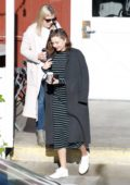 Miranda Kerr wears a black and white striped dress to lunch with her friends in Brentwood, Los Angeles