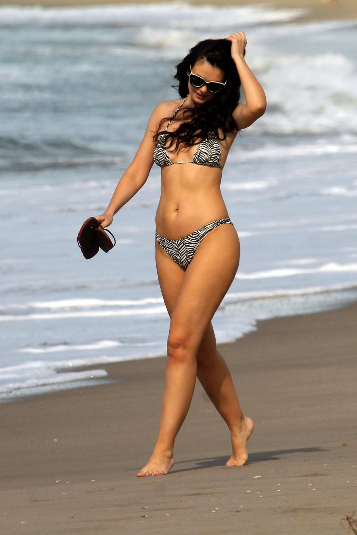 Natasha Blasick enjoys a stroll on the beach wearing a bikini in Malibu, California