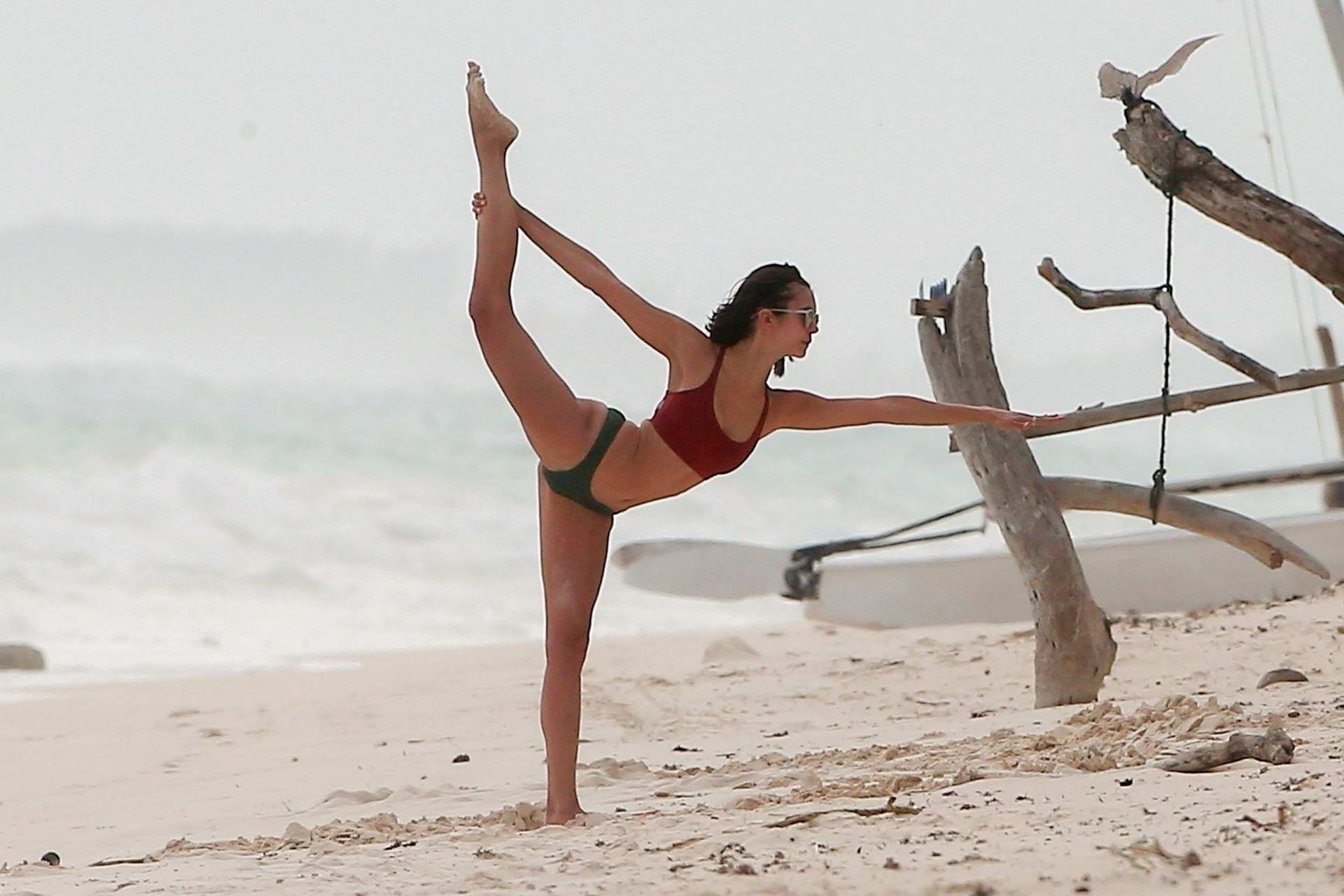 Nina Dobrev enjoys some beach yoga and cartwheels with her friends in Tulum, Mexico