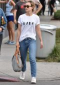 Olivia Wilde is seen out with a friend wearing classic white tee with blue jeans in West Hollywood, Los Angeles