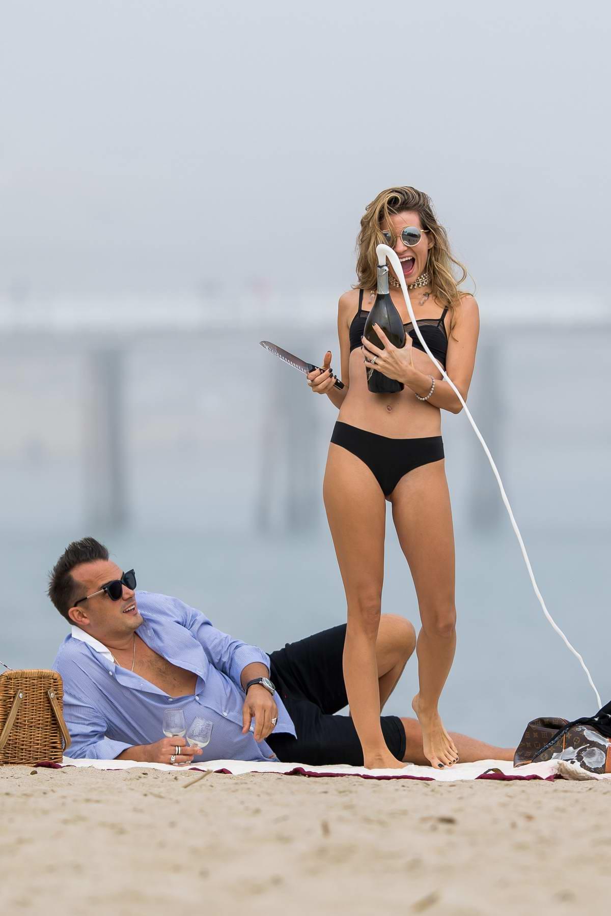 Rachel McCord sizzles in a black bikini as she celebrate New Year's Eve with husband Rick Schirmer on the beach in Malibu, California