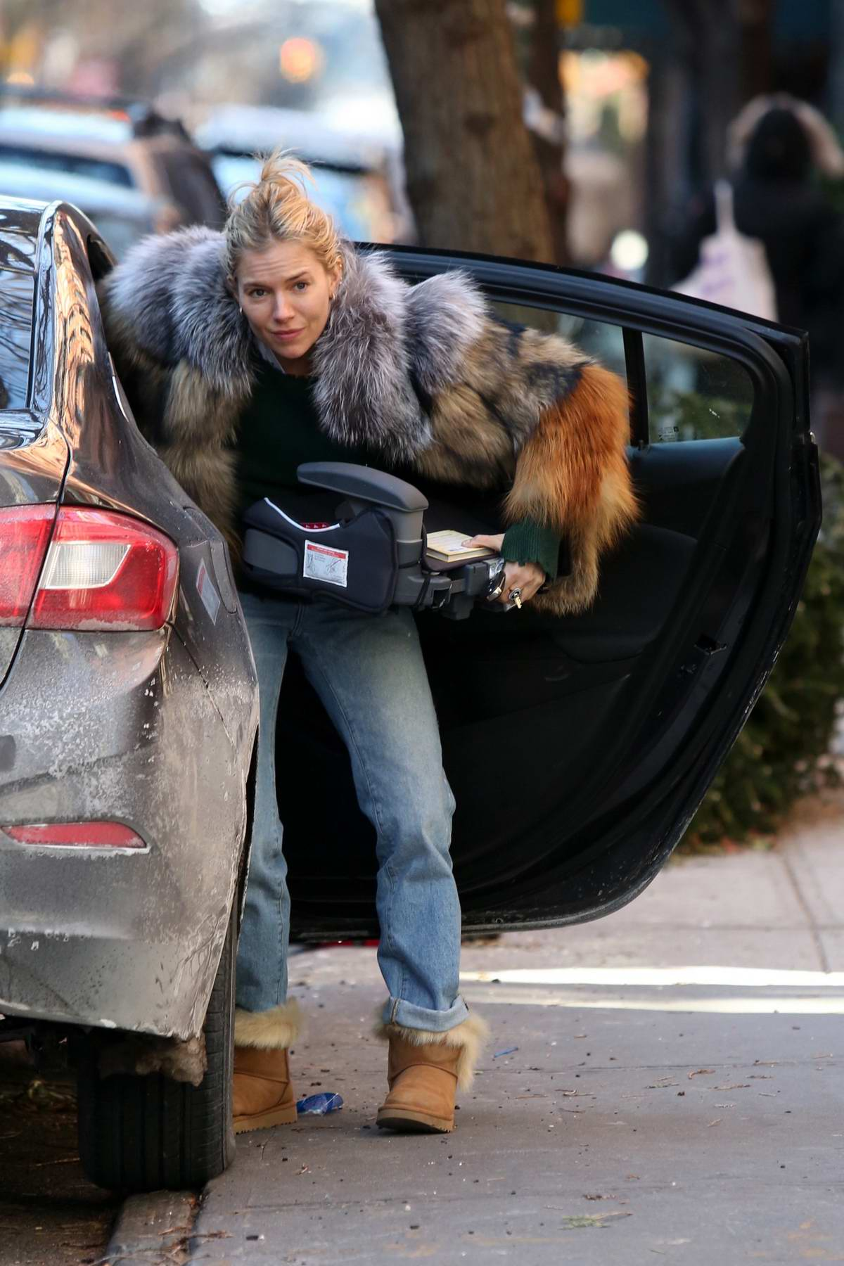 Sienna Miller in a fur jacket and fur boots unloading a car in the West Village, New York City