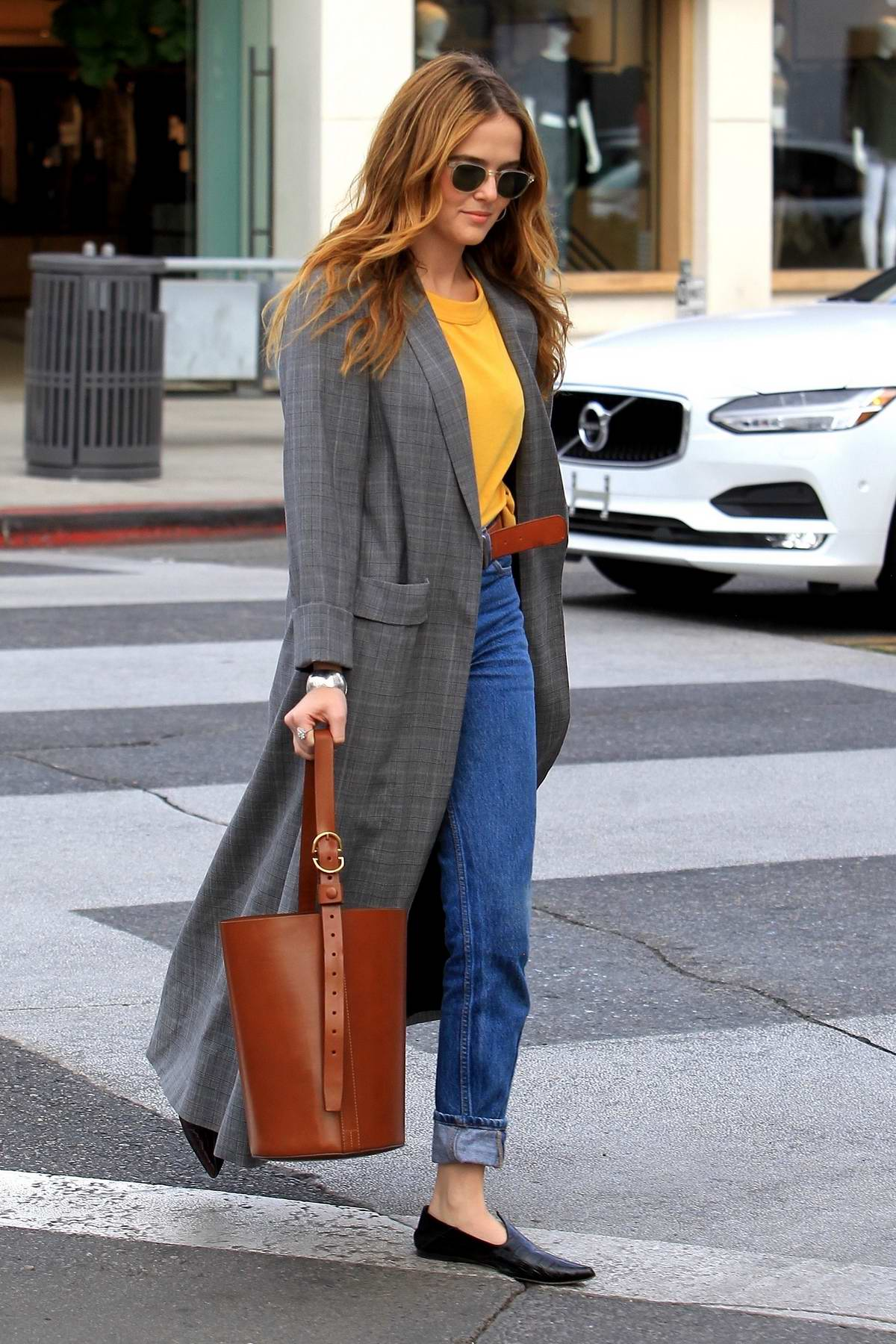 zoey deutch dressed in a full length plaid trench coat ...