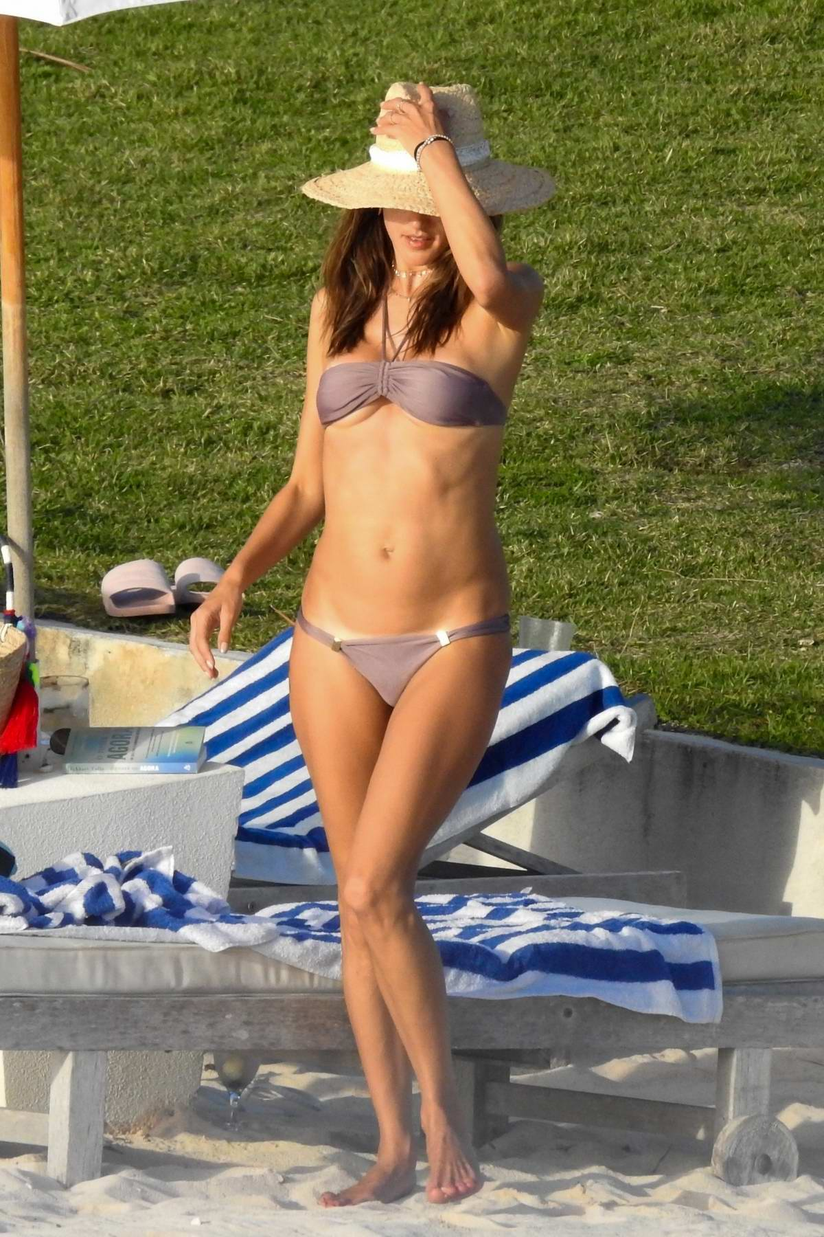 Alessandra Ambrosio wears a purple bikini while she spends a day relaxing on the beach with her family in The Bahamas