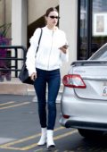 Alessandra Ambrosio wears blue jeans and white knit jacket to match with her white boots as she leaves a spa in Beverly Hill, Los Angeles
