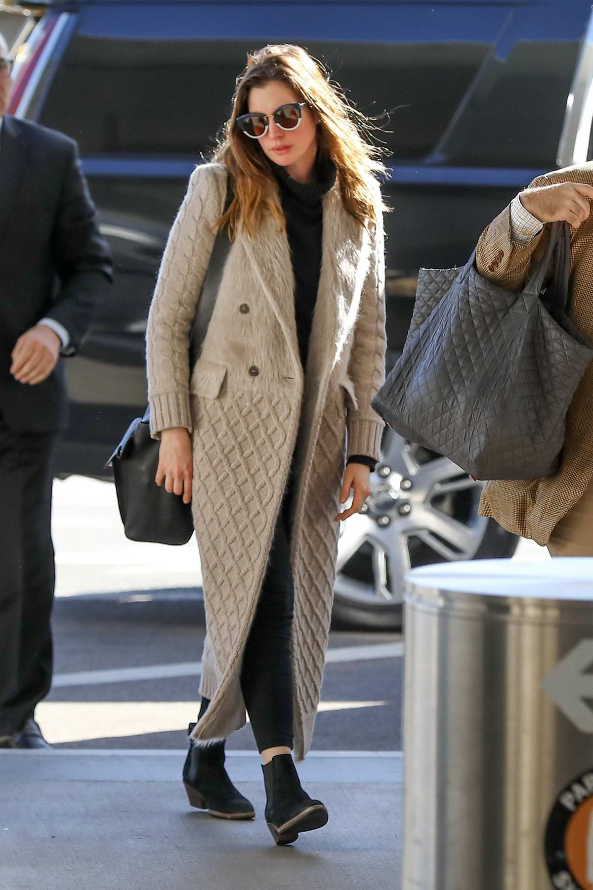 Anne Hathaway wears a knit trench coat while arriving at LAX airport, Los Angeles