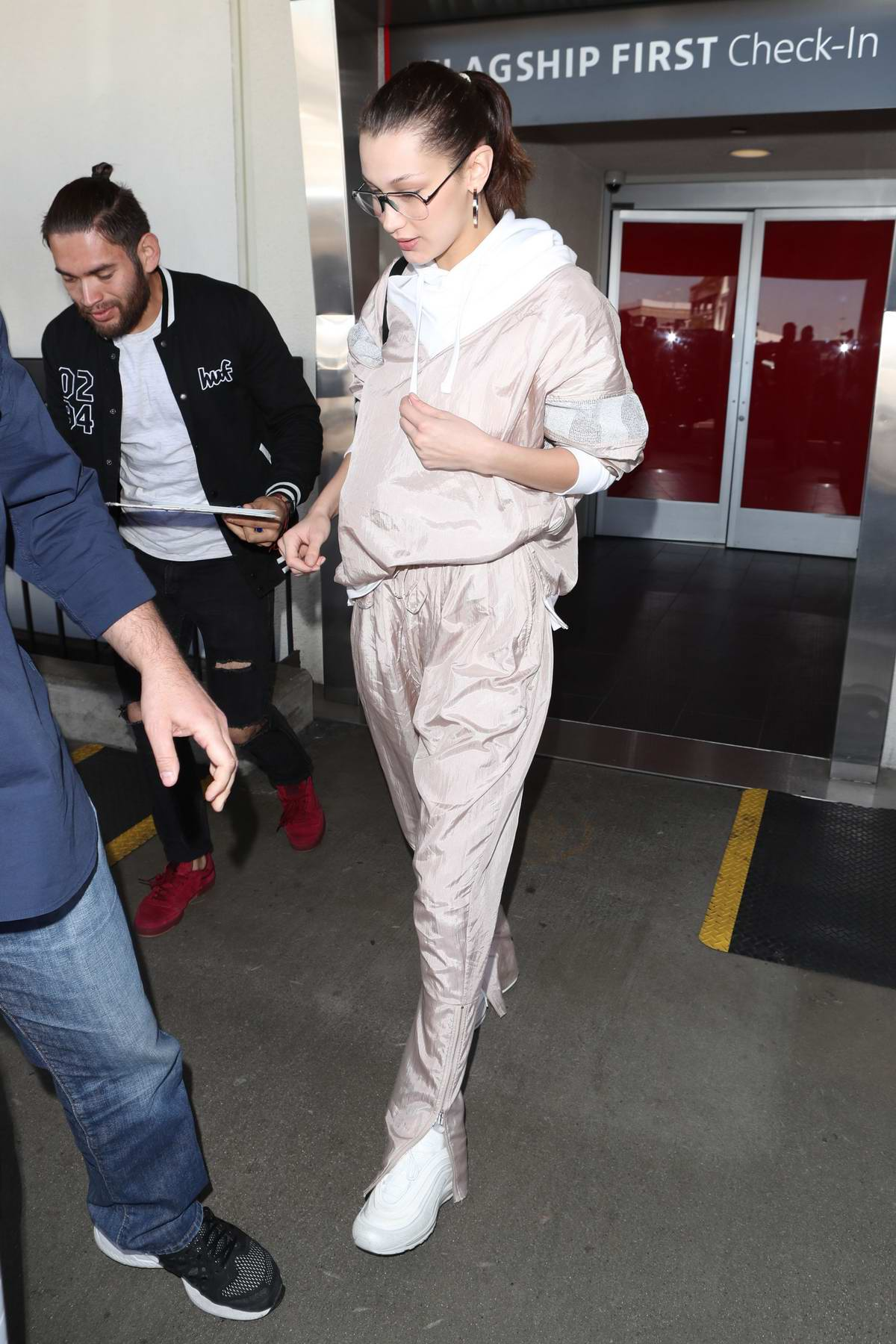 Bella Hadid spotted at LAX airport in a light pink jumpsuit as she touch down in Los Angeles