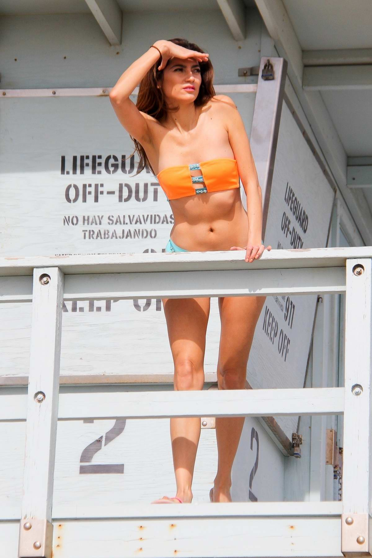 Blanca Blanco in an orange bikini plays lifeguard for a day in Malibu, California