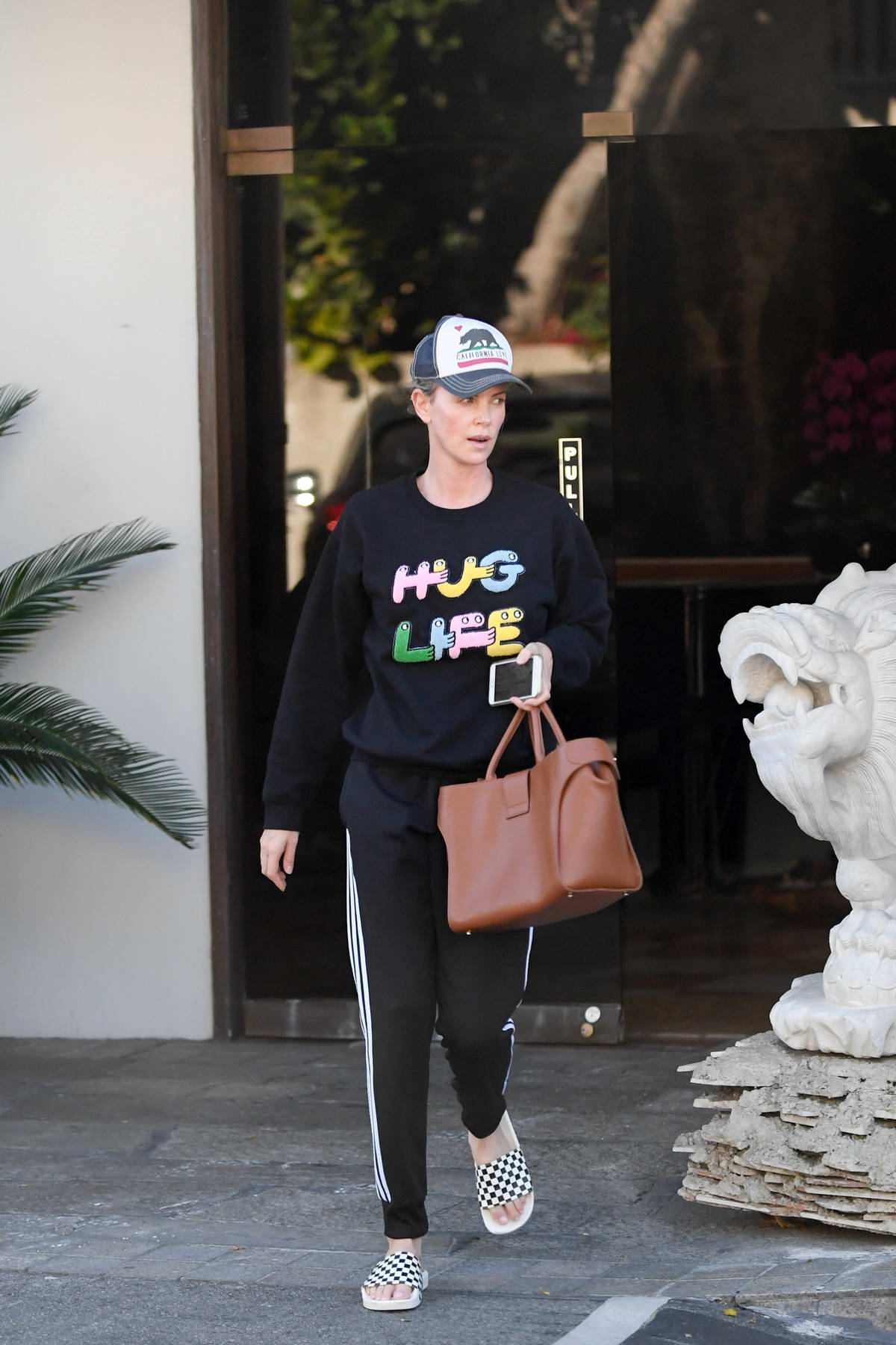 Charlize Theron sports a hug life sweatshirt as she leaves a Korean spa in Koreatown, Los Angeles