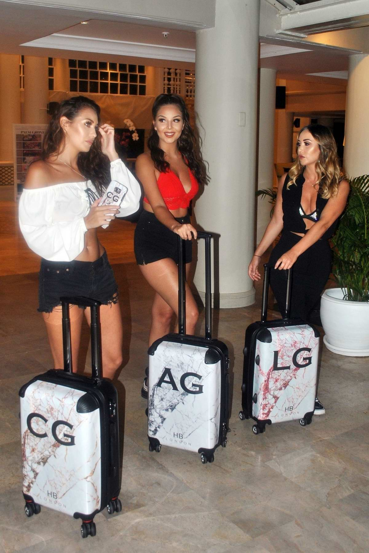 Chloe, Amelia and Lauryn Goodman shows of their personalized luggage at a resort in Thailand