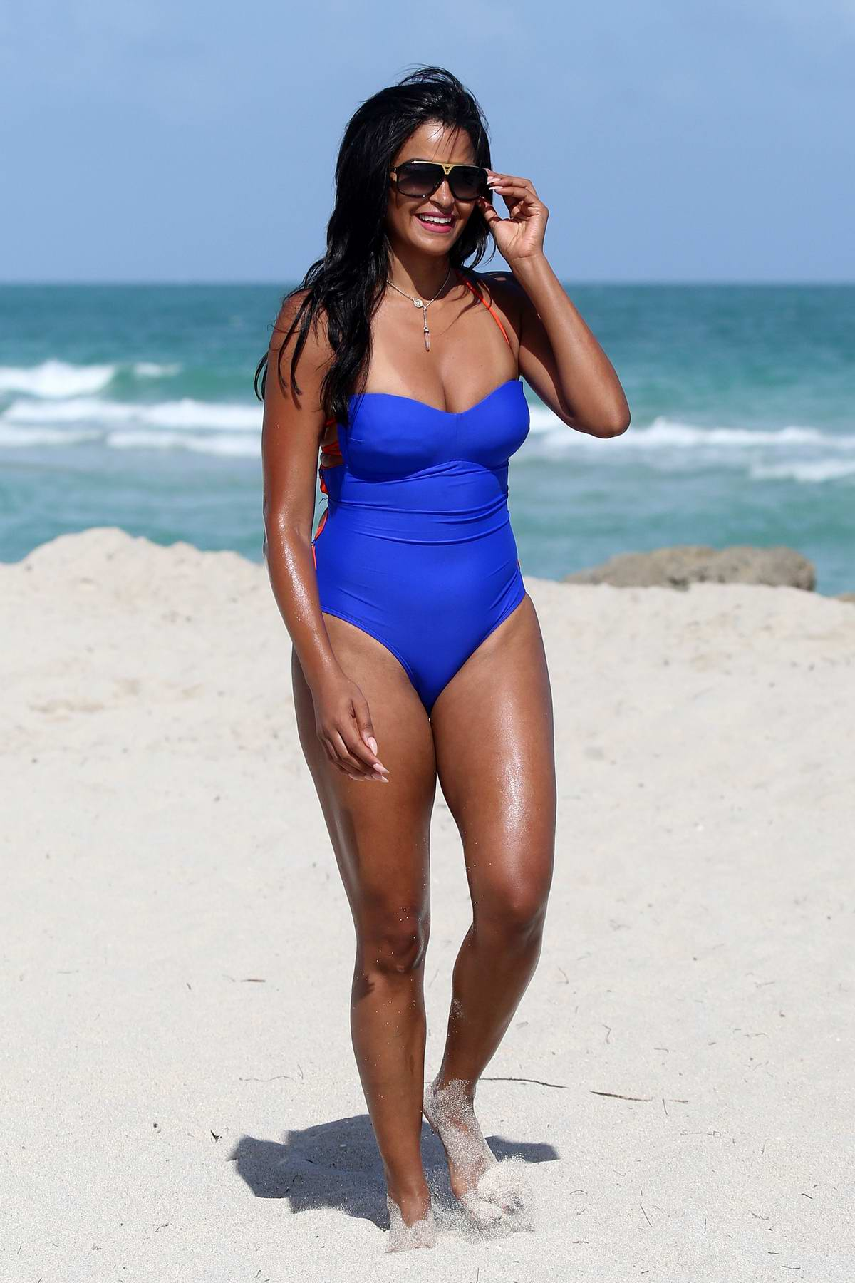 Claudia Jordan wears a blue swimsuit while soaking up the sun on the beach in Miami, Florida