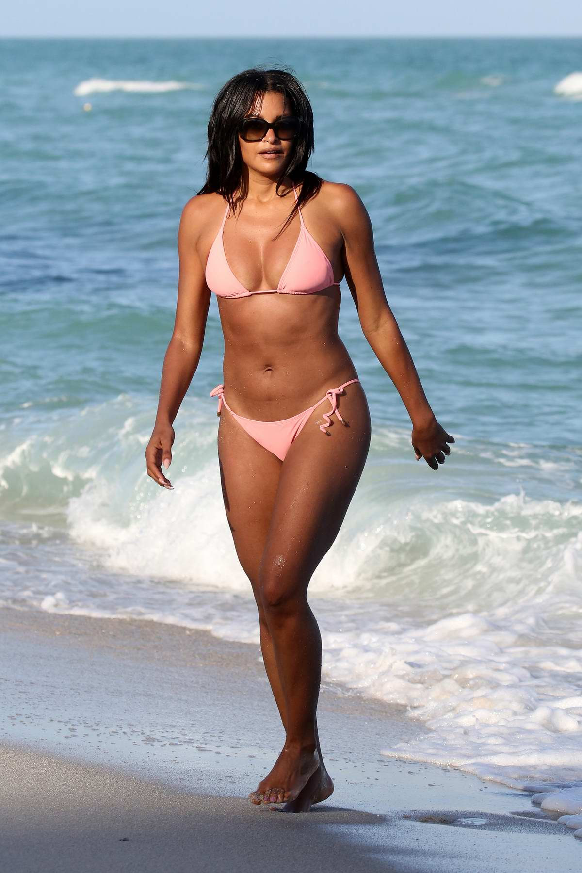 Claudia Jordan wears a pink string bikini while strolling on the beach in Miami, Florida