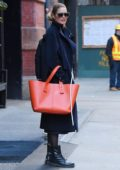 Doutzen Kroes rocks a blue trench coat with an orange bag as she heads out in New York City