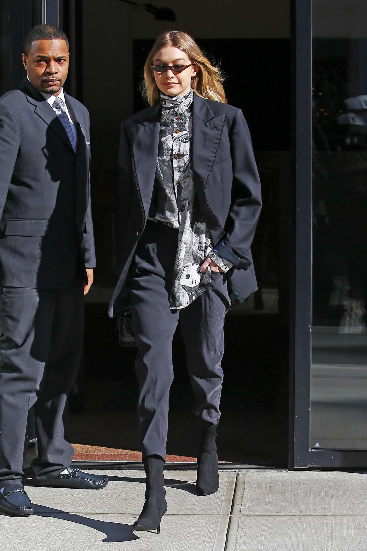 Gigi Hadid leaves her apartment in a dark blue pantsuit in New York City