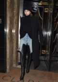 Hailey Baldwin heads out of Claridge Hotel in a pair of thigh-high black leather boots during London Fashion Week in London