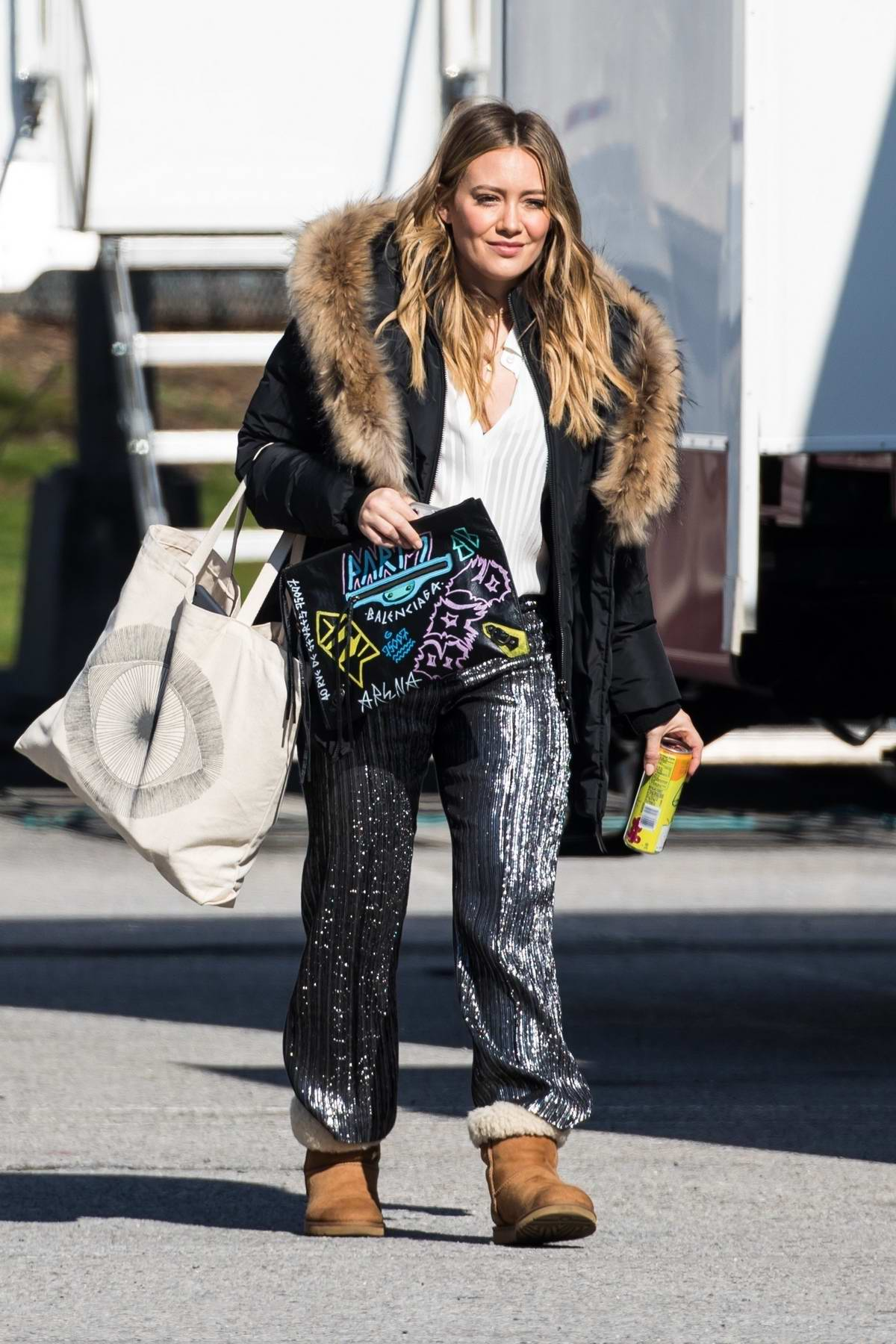 Hilary Duff spotted wearing a fur trimmed jacket with a pair of shiny pants and UGG boots on the set of 'Younger' in New York City