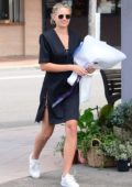 Jesinta Campbell Franklin smiles for the camera while picking flowers in a black dress in Sydney, Australia