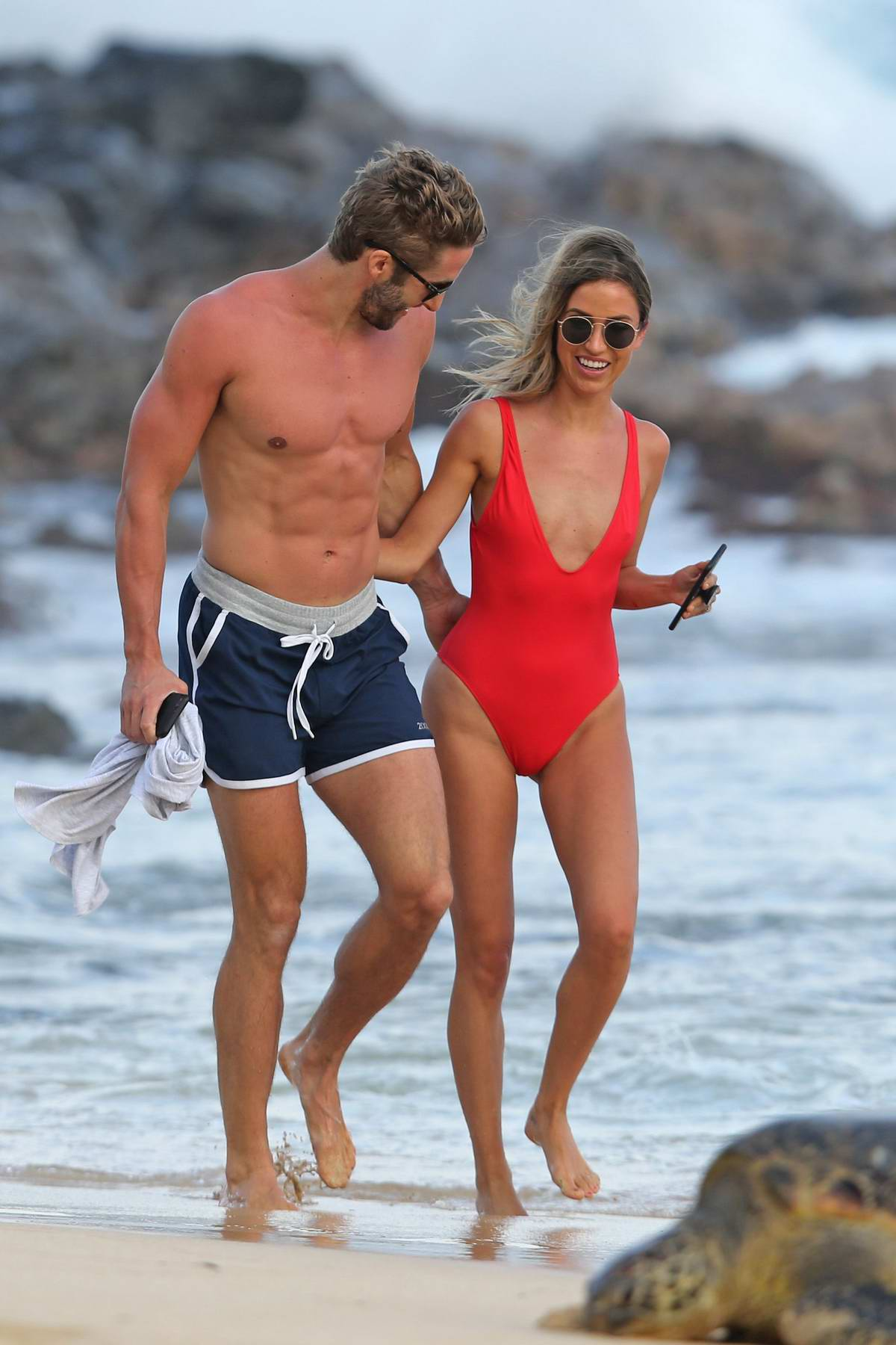 Kaitlyn Bristowe wears a red swimsuit while she enjoys a stroll on the beach with Shawn Booth in Hawaii