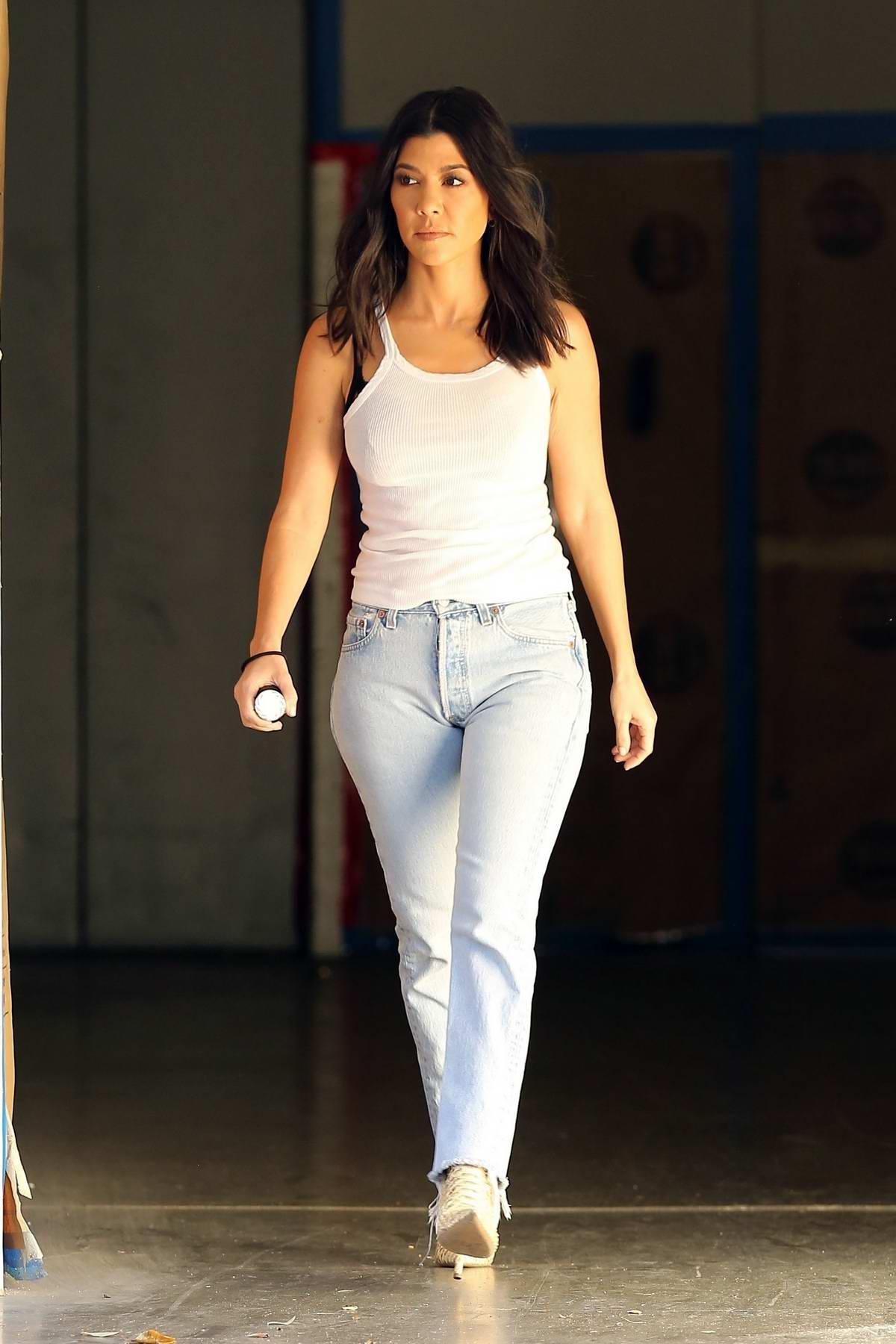 Kourtney Kardashian visits an office building wearing a white tank, blue jeans in Sherman Oaks, Los Angeles