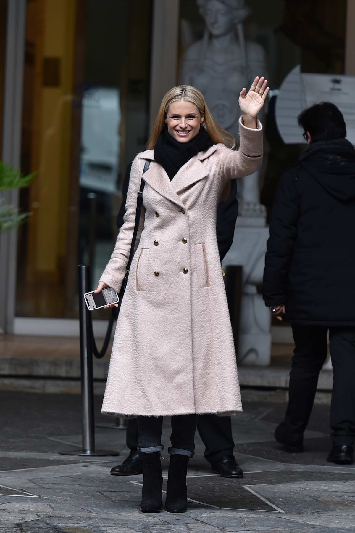 Michelle Hunziker waves to the cameras as she leaves her hotel in Sanremo, Italy