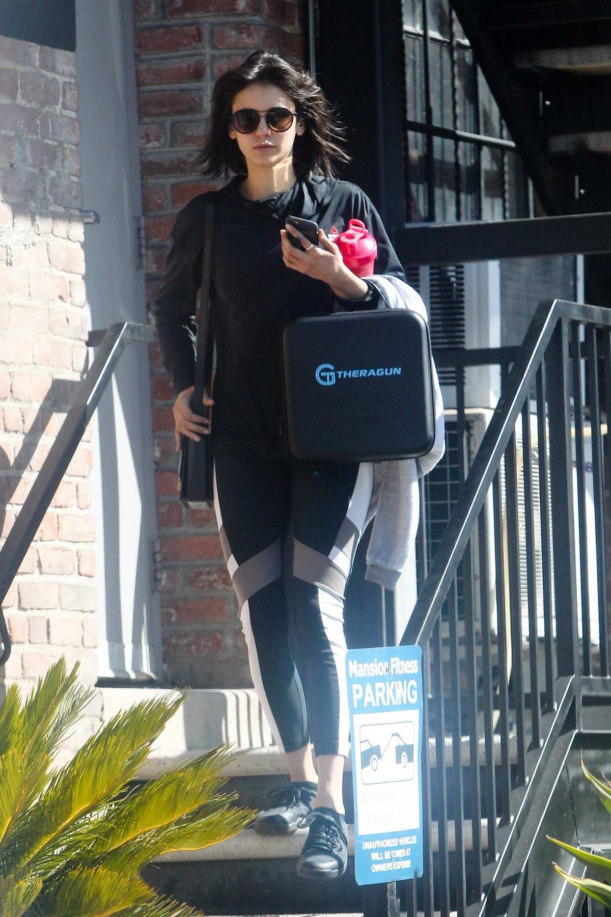 Nina Dobrev wraps up a morning workout as she exits Mansion Fitness with a TheraGun in Los Angeles