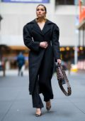 Olivia Culpo wearing a Jacquemus coat, Johanna Ortiz jumpsuit with Jimmy Choo shoes and a Dior handbag in midtown New York City