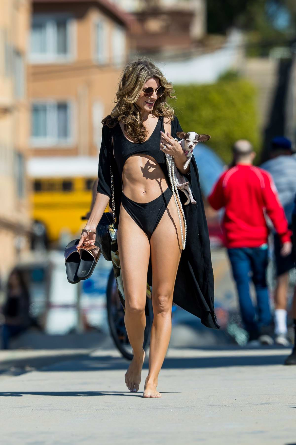 Rachel McCord wears a black bikini as she hits the beach with her dog in Santa Monica, California