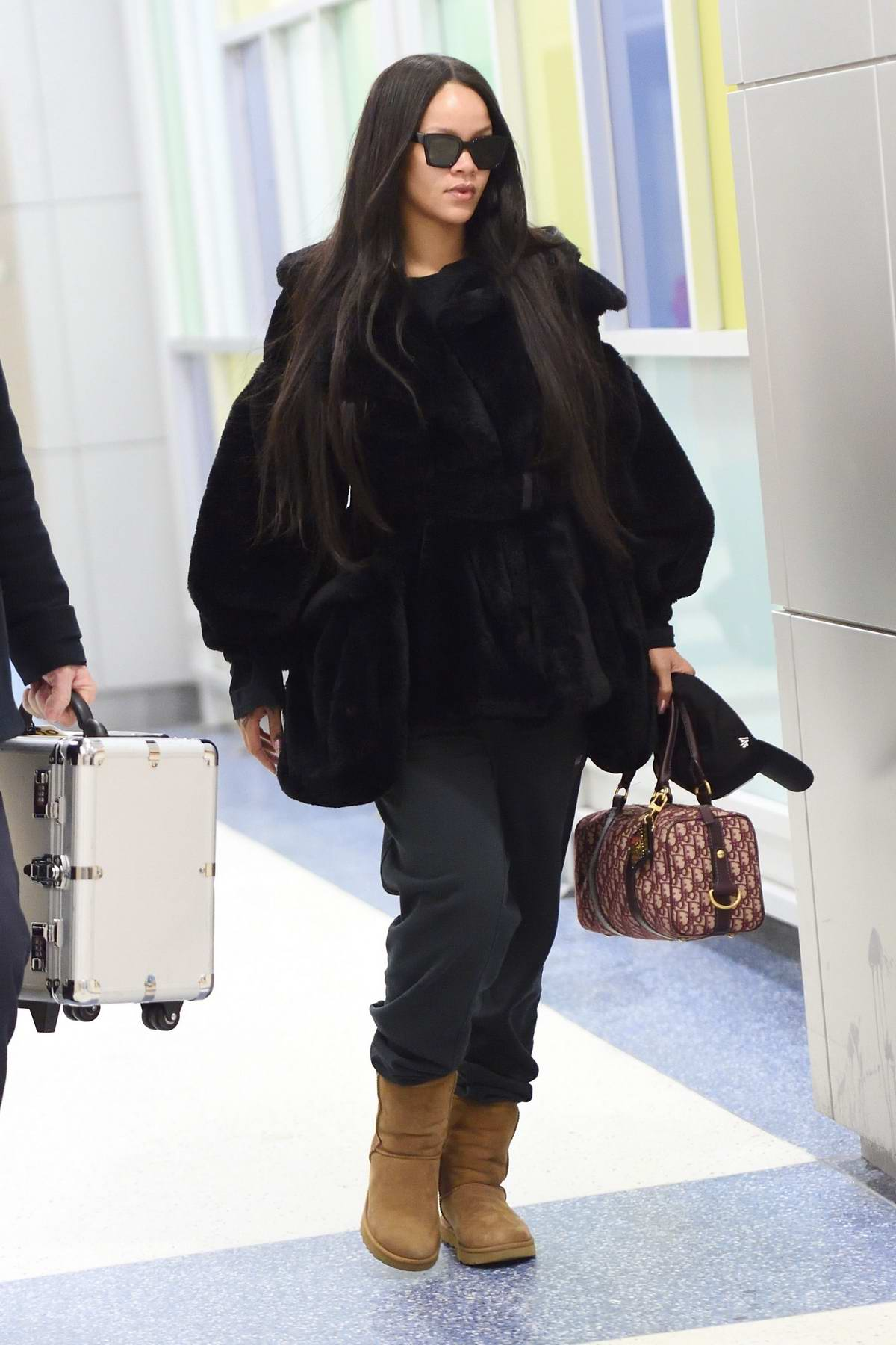Rihanna looks chic in her black fur coat and sweatpants with UGG boots as she arrives at JFK airport in New York City