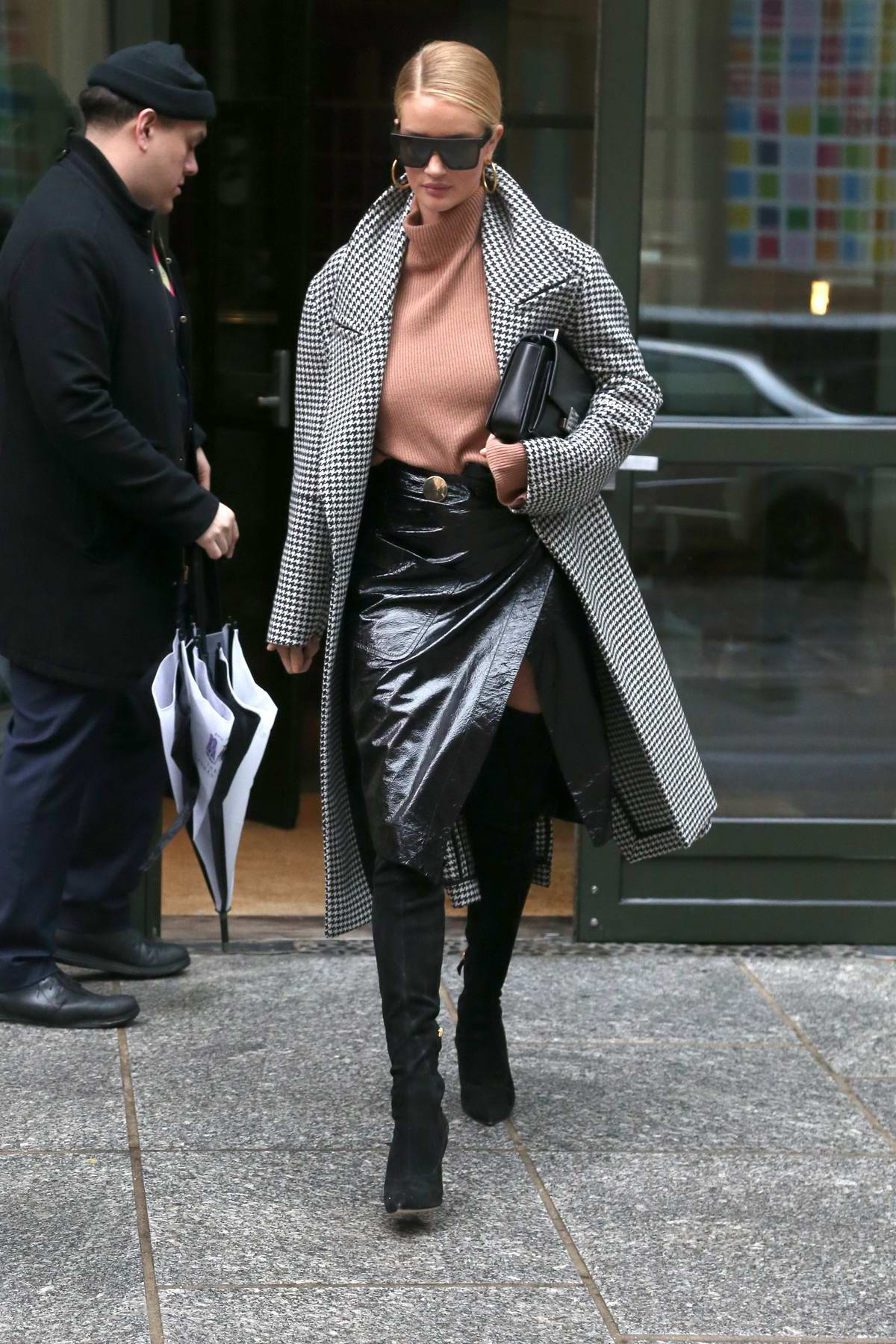Rosie Huntington-Whiteley leaves her hotel wearing a checkered trench coat with black leather skirt and thigh high boots in New York City