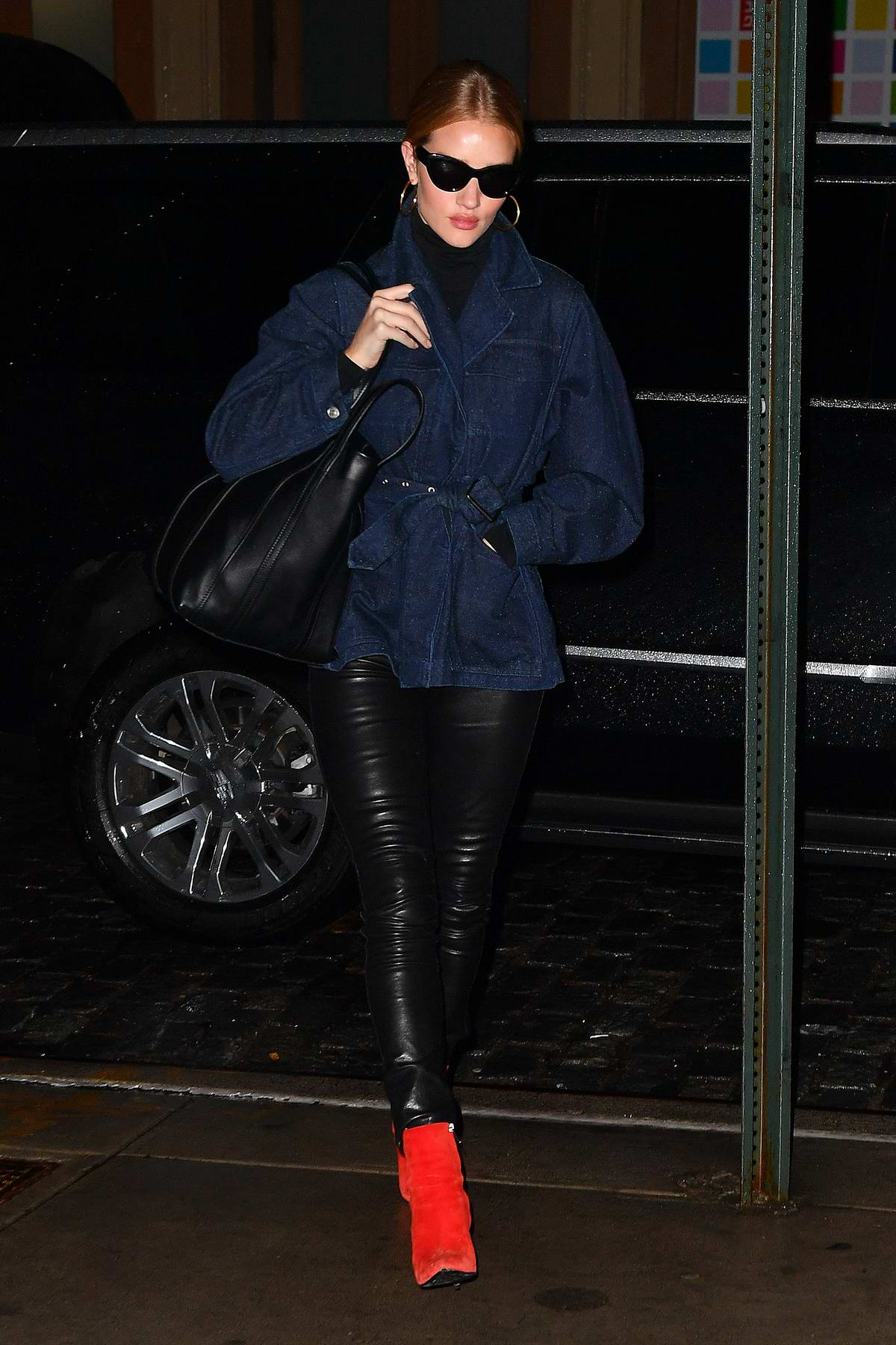 Rosie Huntington-Whiteley wears bright red boots with a denim jacket and leather pants during a night out in New York City