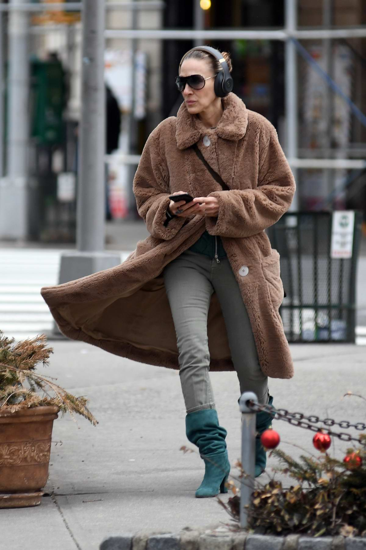 Sarah Jessica Parker wearing headphones and a cozy brown coat while out in New York City