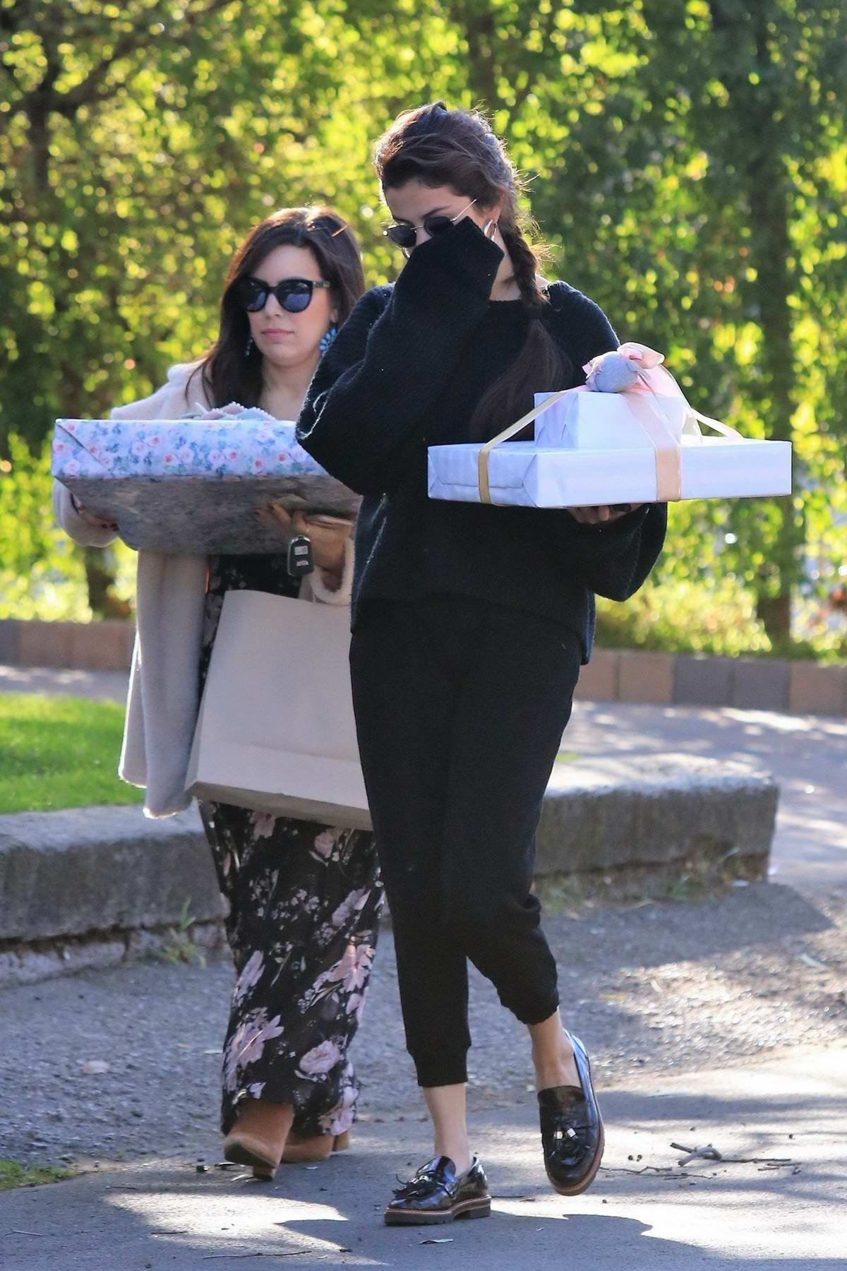 Selena Gomez arriving to a party bearing gifts in Studio City, Los Angeles
