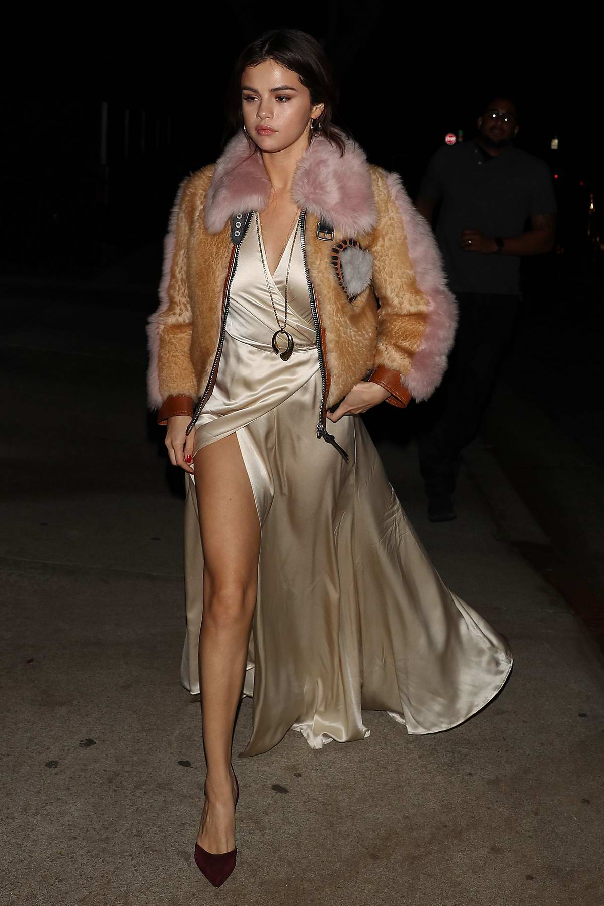 Selena Gomez wore a cream satin dress with a cropped fur jacket during a night out with friends in Los Angeles