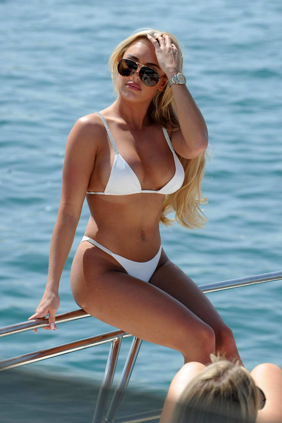 Amber Turner wears a white bikini as she enjoys a day with her friends on a yacht in Dubai
