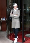 Bella Hadid leaves her hotel in a plaid coat and white hat in Paris, France
