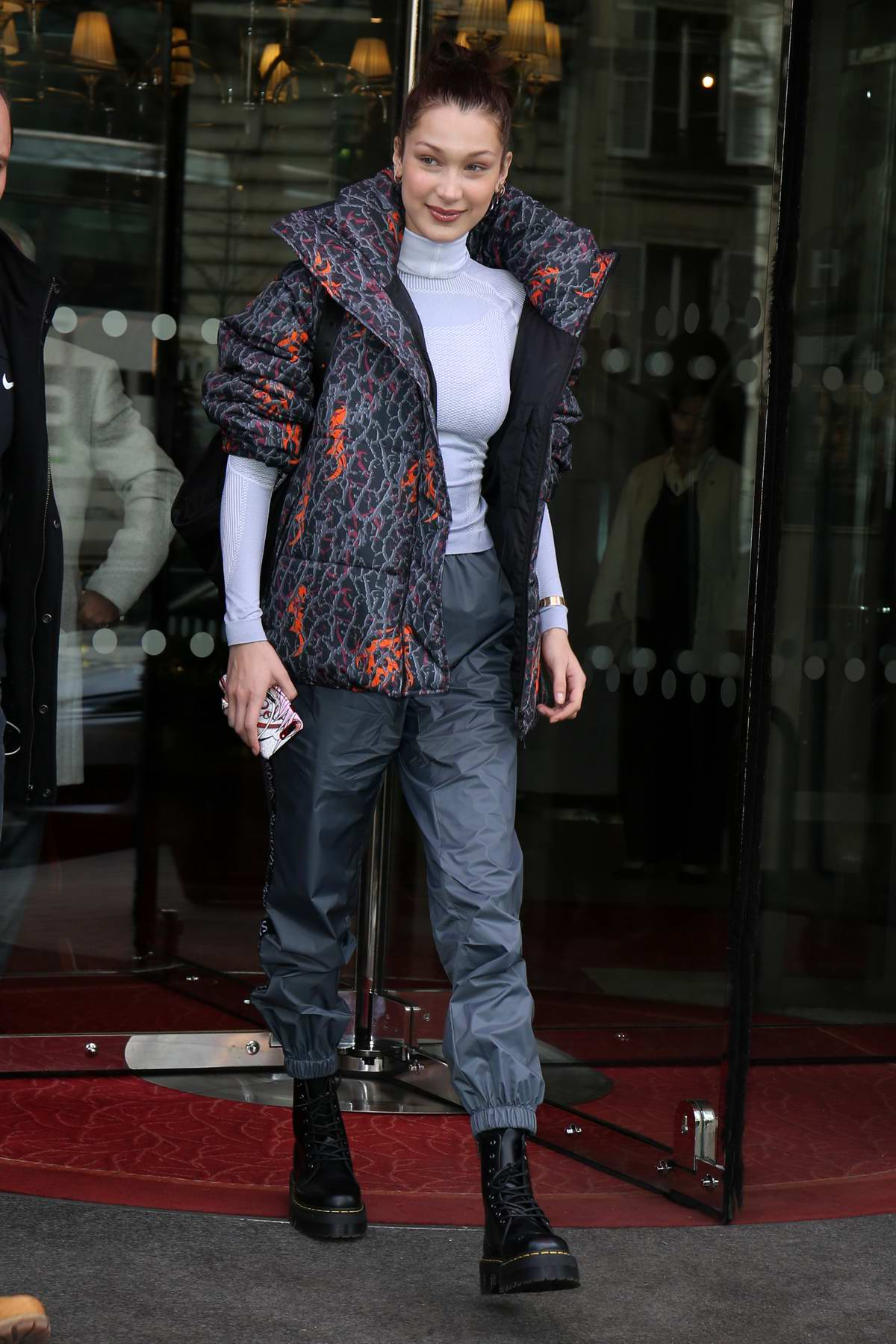 Bella Hadid wearing a patterned puffer jacket with Sankuanz track pants while she greet her fans outside The Royal Monceau Hotel in Paris, France